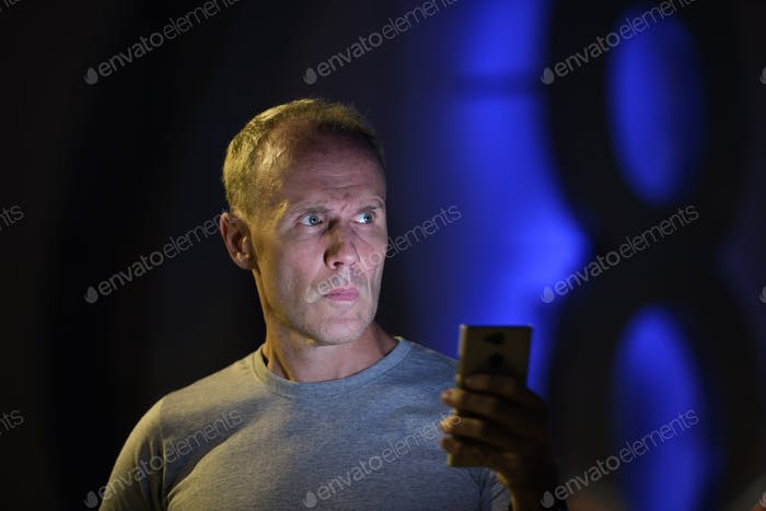 Man using phone while thinking outdoors at night