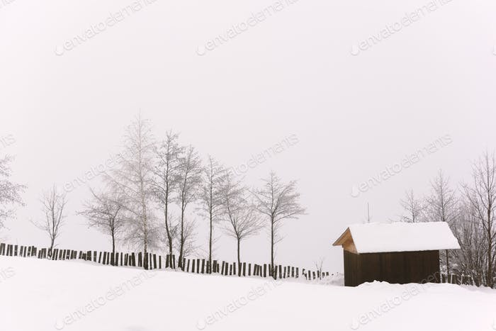 Minimalistic winter landscape with wooden house