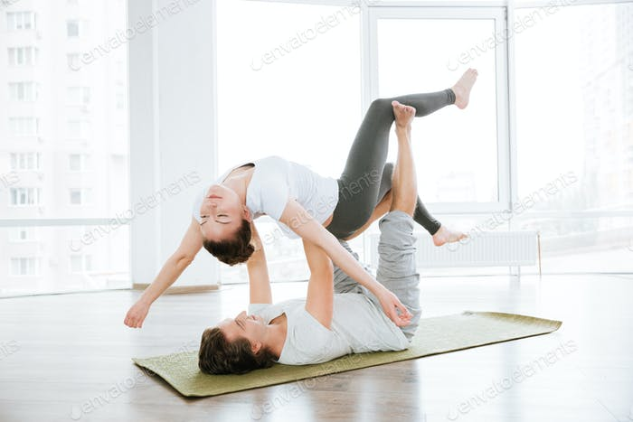 Relaxed couple practicing acro yoga exercises in studio