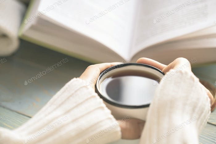 Girl reading book and drinking tea in winter