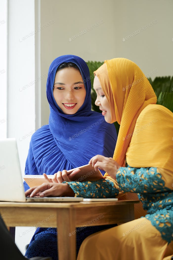 Muslim students doing homework in cafe