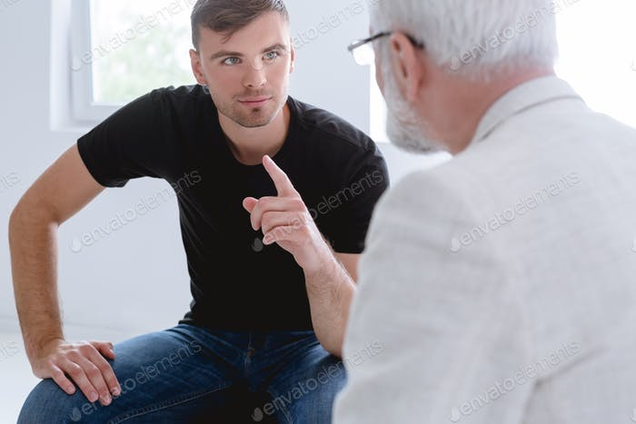 Young man and professional counselor during psychotherapy for people with ptsd