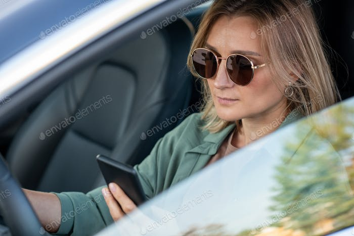 Young contemporary woman driving car and texting