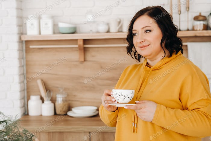 a woman in an orange sweatshirt drinks coffee in the kitchen at home
