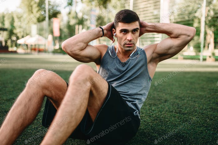 Male athlete doing exercises on the press outdoor