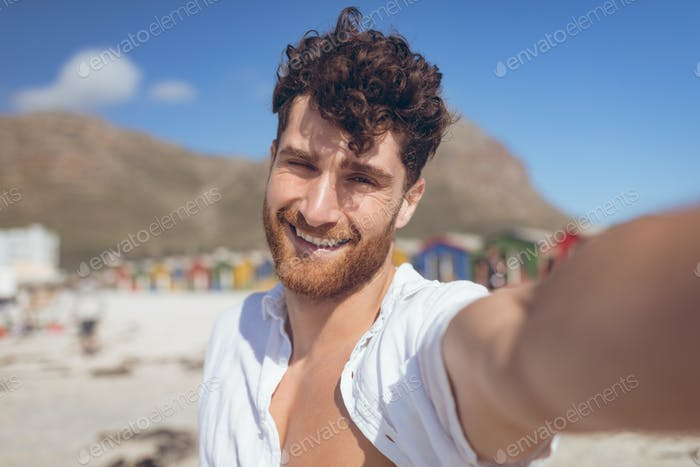 Happy young man taking a selfie standing at beach on a sunny day