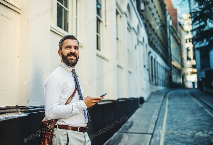 Hipster businessman standing on the street in London, holding smartphone.