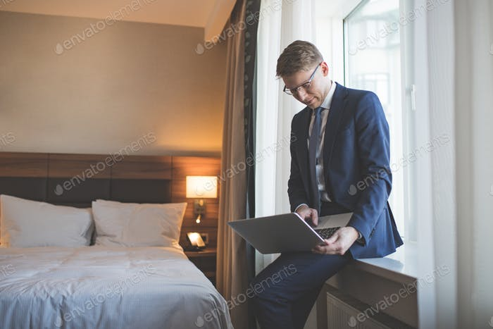 Young businessman in suit with laptop