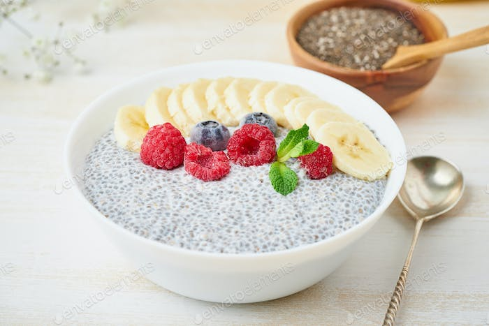 Banner with Chia pudding in bowl with fresh berries raspberries, blueberries.