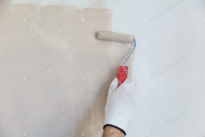 Maler Hand in weißen Handschuh Malerei eine Wand mit Farbrolle