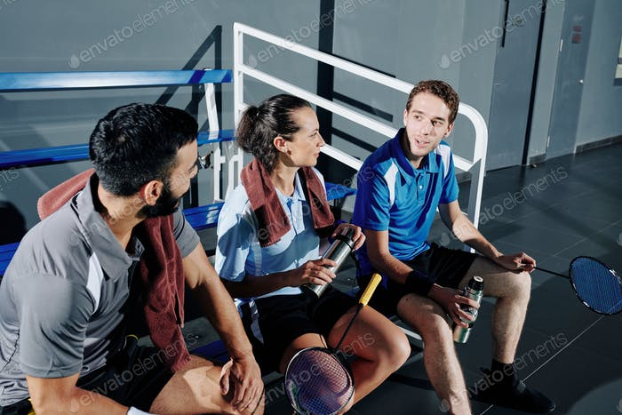 Badminton players resting on bench