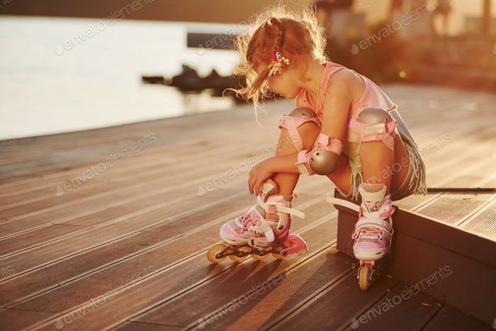 Happy cute kid with her roller skates. Unbelievable sunlight