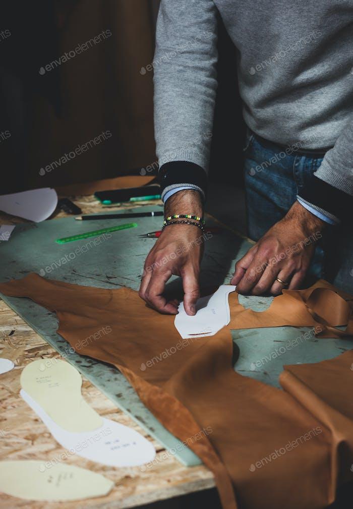 Schuhdesigner arbeitet mit Leder.