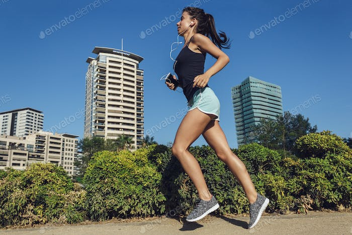 Beautiful Fitness Girl Running In The City With Urban Background Of Skyscrapers