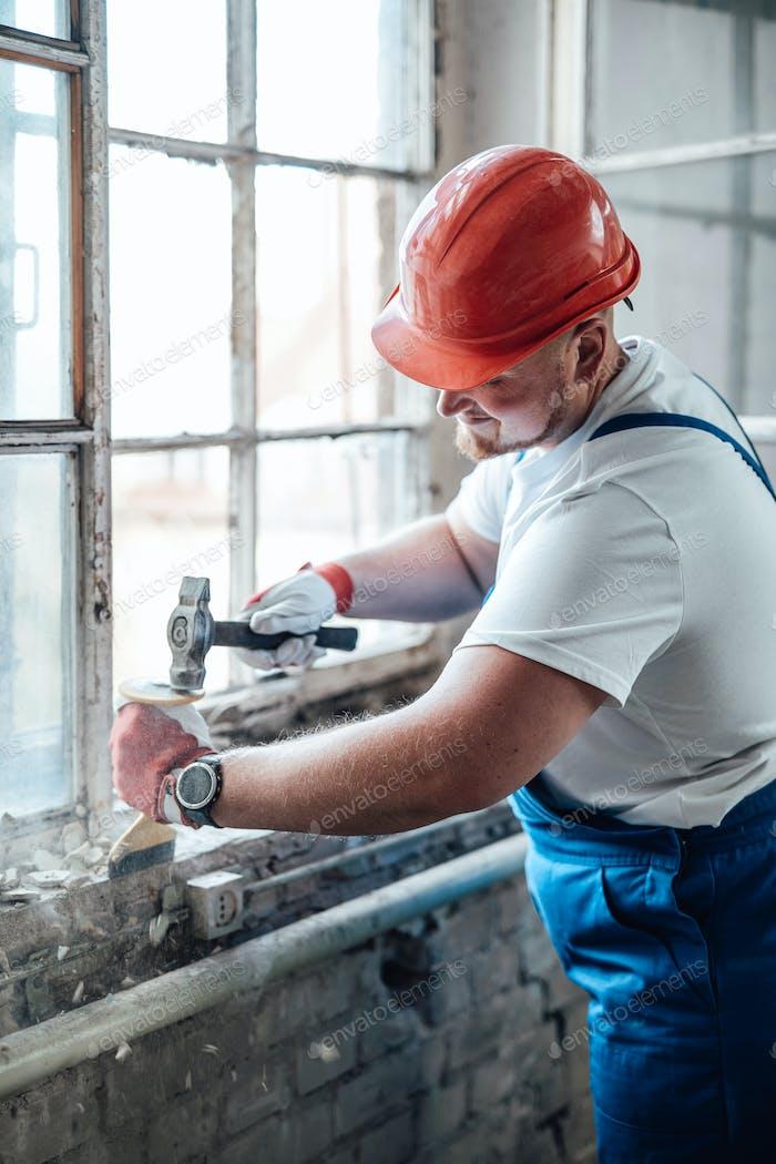 Auftragnehmer mit einem Hammer, um alte Ziegelwände zu zerstören