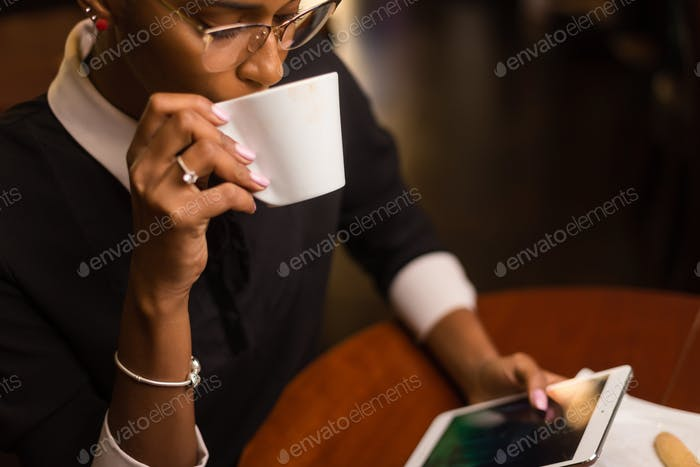 Black african american young yoman drinking coffee and using a t