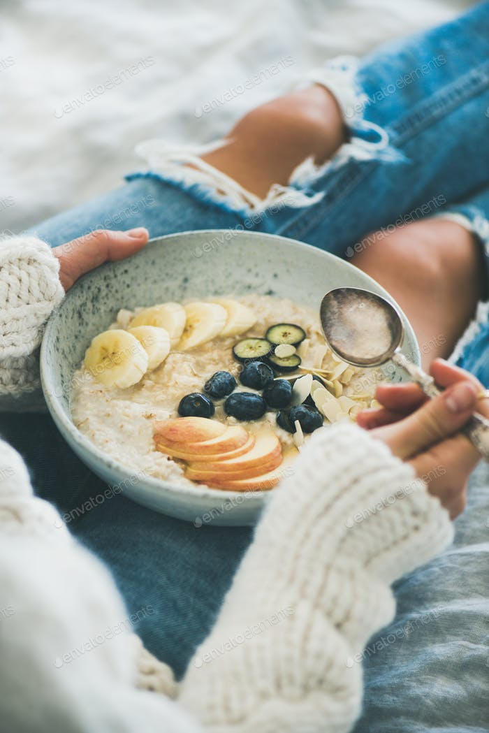 Woman in jeans and sweater eating healthy vegan breakfast, close-up