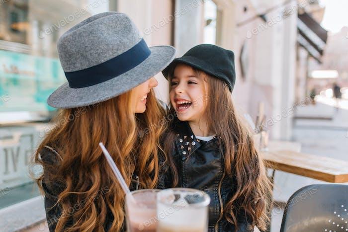 Zwei langhaarige lockige Schwestern schauen sich mit Liebe an und genießen den sonnigen Morgen im Freien
