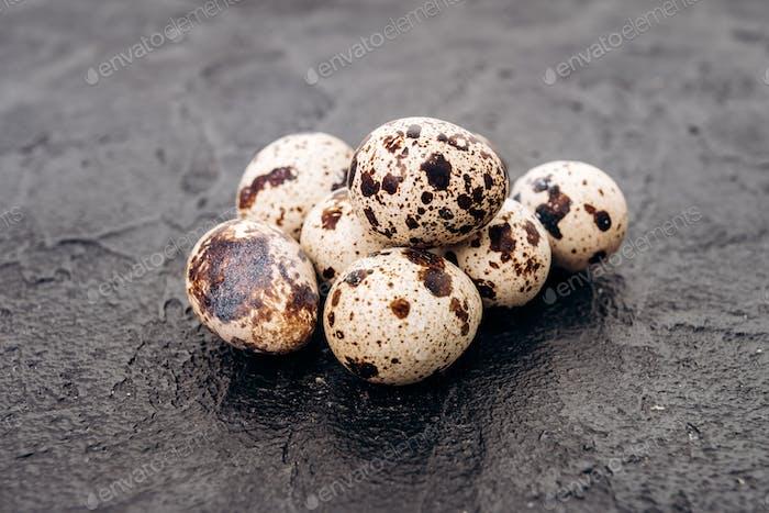 Quail eggs on a black background. Several quail eggs lie on a black stone background