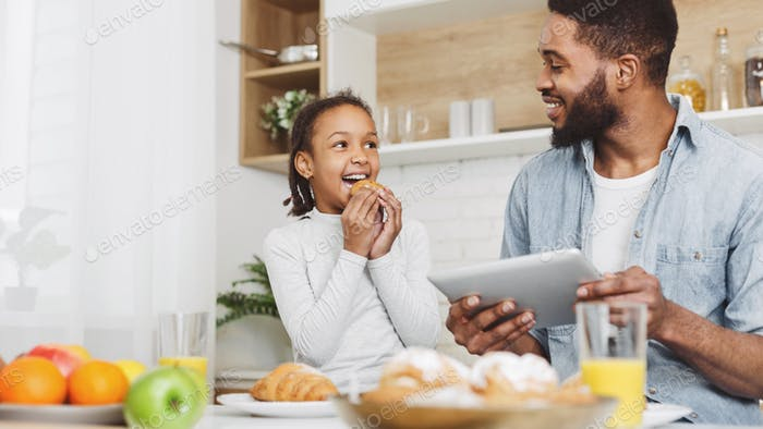 Father and daughter eating sweets and looking for new recipes