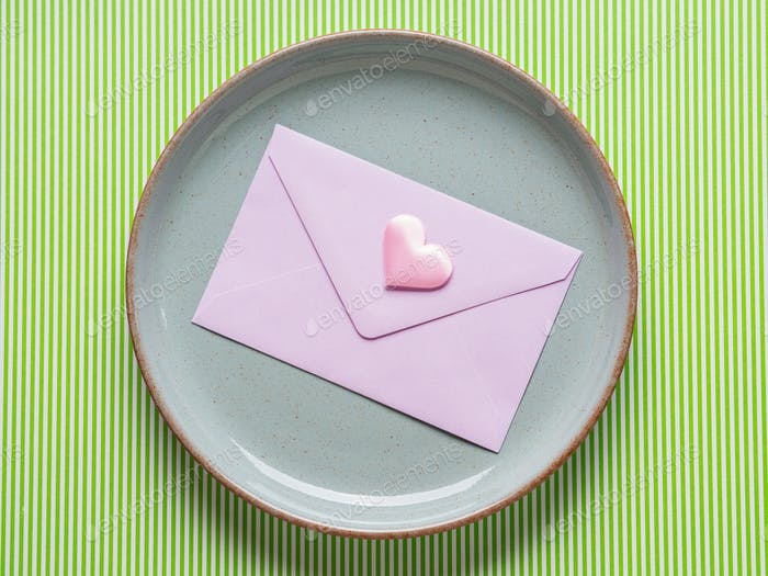 Gray dish with pink envelope on green