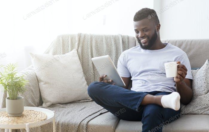 Fröhlicher schwarzer Mann liest Nachrichten auf digitalem Tablet mit Kaffee