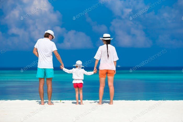 Young family of three on white beach during tropical vacation