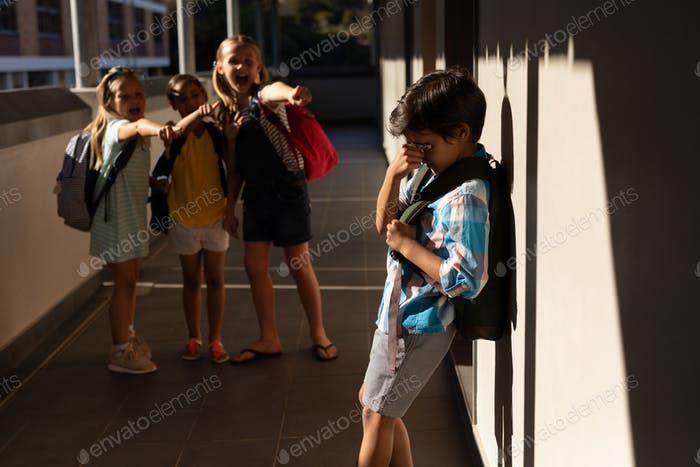 Front view of school friends bullying a crying boy in hallway of elementary school