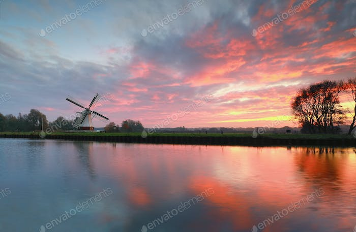 dramatic sunrise over white windmill by river