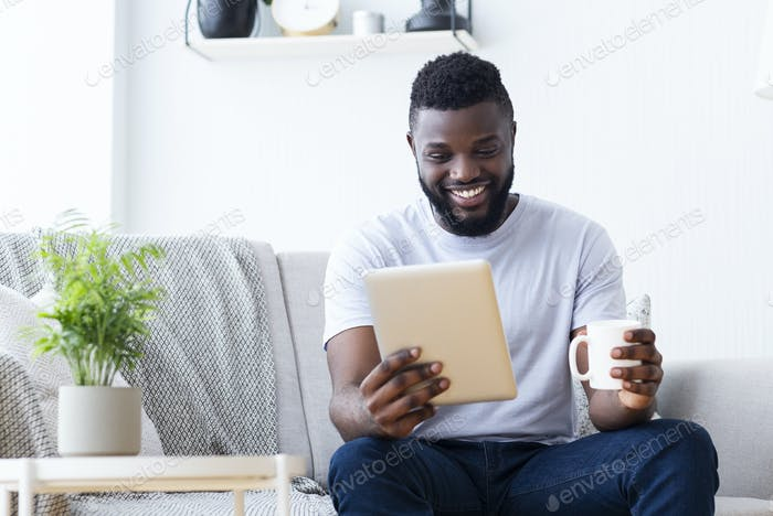 African millennial guy enjoying morning coffee and news on digital tablet