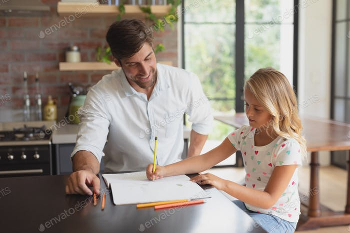 Front view of Caucasian father helping his daughter with homework in a comfortable home