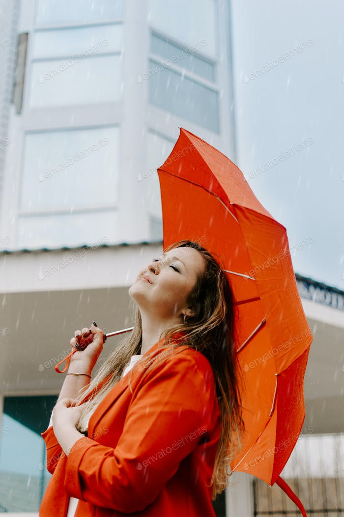 Mental Health concept. Portrait of young happy woman in red under red umbrella breathing in the