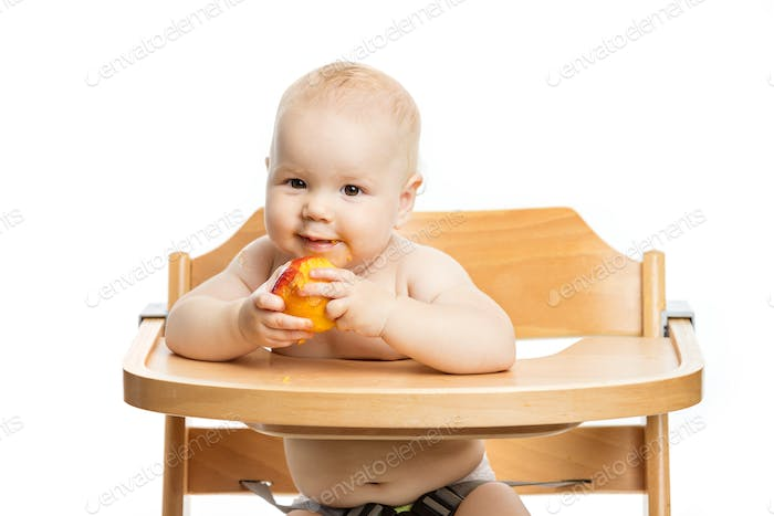 Cute baby girl eating peach while sitting in high chair