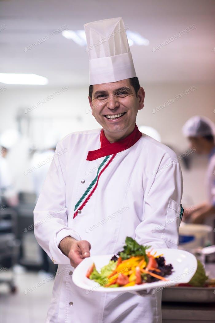 Chefkoch zeigt einen Teller mit leckerem Essen