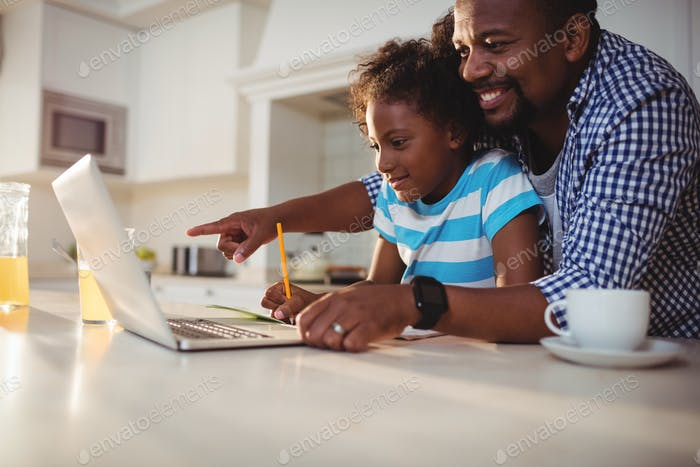 Father using laptop while assisting his daughter with homework