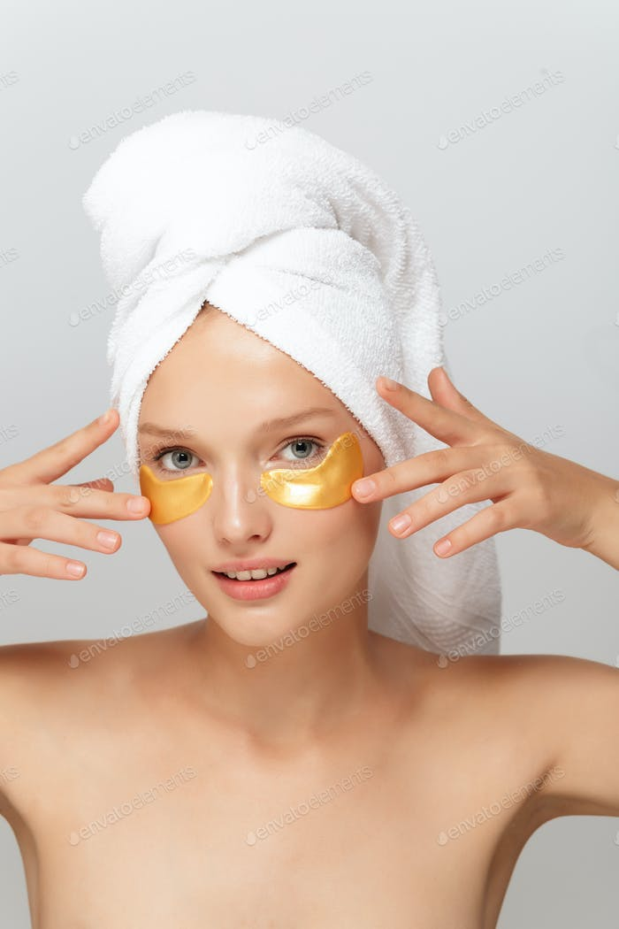 Young attractive lady with white towel on head without makeup wi