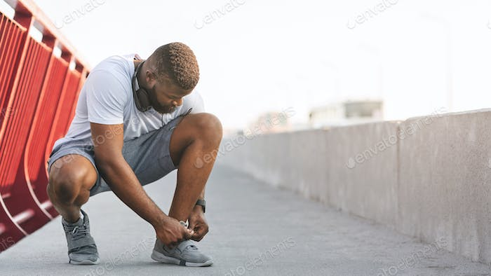 Afro guy checking on his shoelaces on bridge