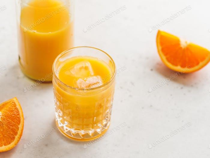 Frischer Orangensaft mit Eiswürfeln in einem Glas auf einem Tisch. Das Konzept der gesunden Ernährung.