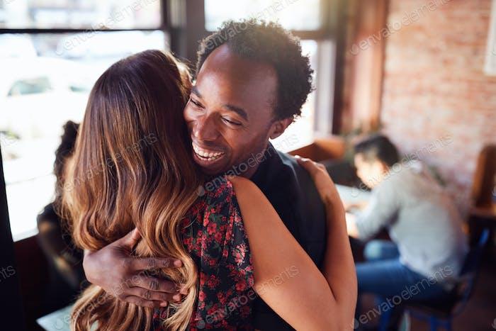Paar Begrüßung jeder andere mit Umarmung als Sie treffen in Coffee Shop