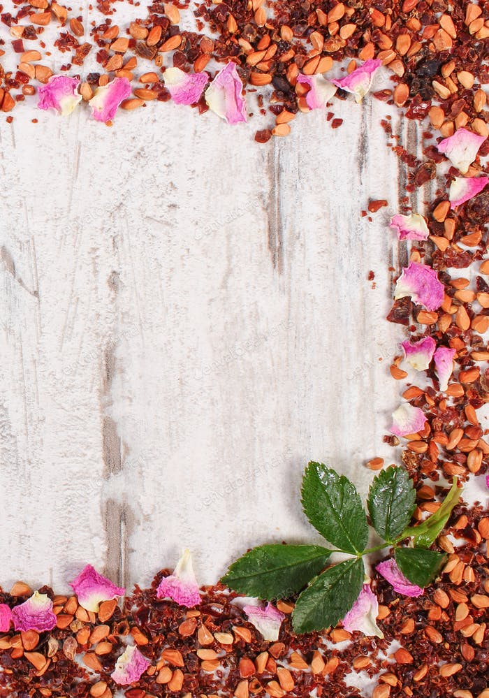 Frame of dried wild rose petals and tea grains, copy space for text on old rustic board