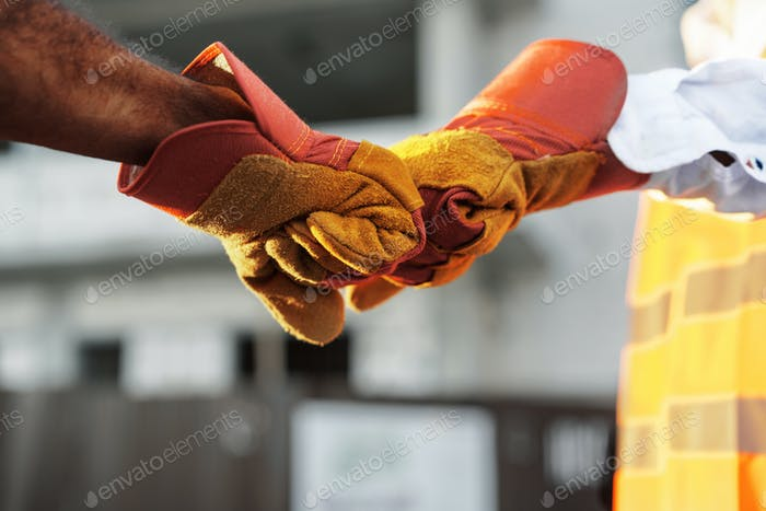Two men engineers in workwear shaking hands against construction site