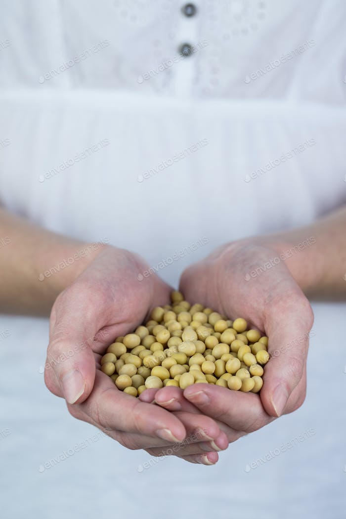 Woman showing handful of chickpeas in close up