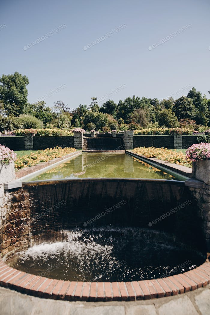 Beautiful old fountains with  water in sunny botanical garden