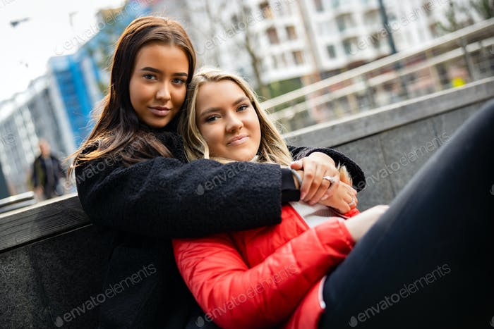 Young Smiling Woman Embracing her Best Friend In City