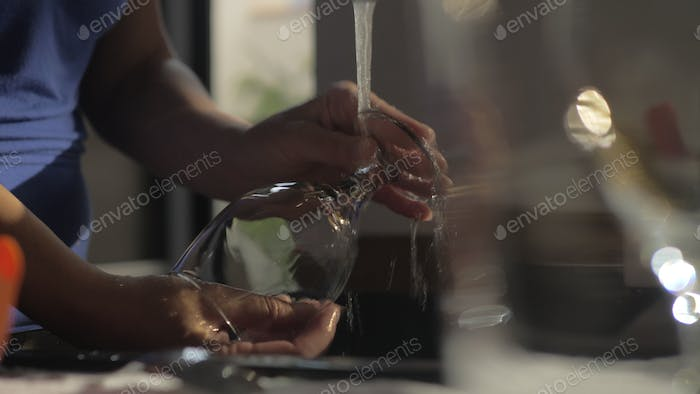 Woman washing wineglass in the kitchen