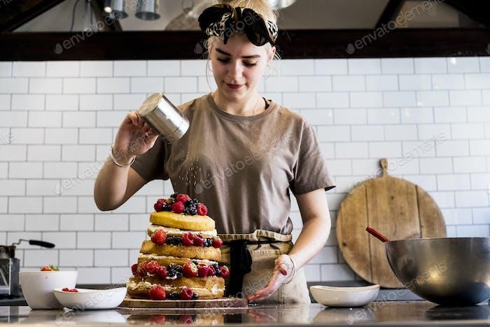 Ein Koch, der in einer kommerziell Küche arbeitet, bestreut Puderzucker über einen geschichteten Kuchen mit frischem Obst.