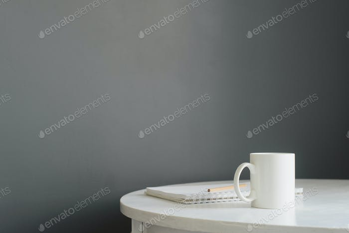 white ceramic coffee cup with notepad and pencil on wooden table