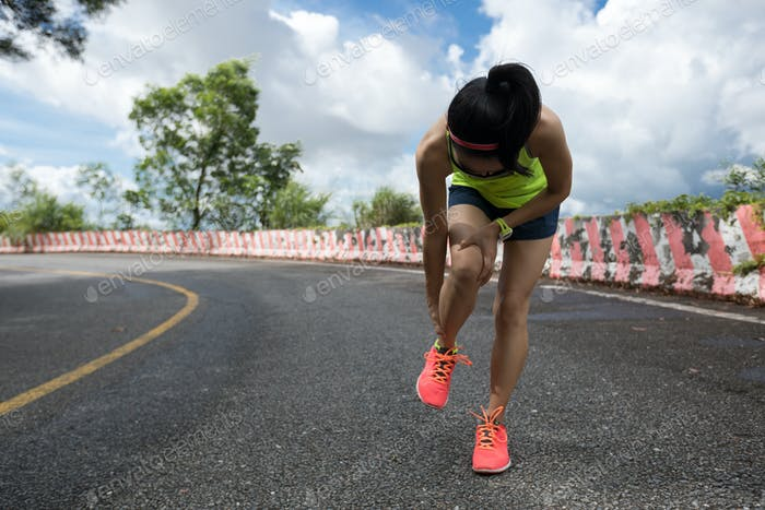 Woman  runner suffering with pain on sports running knee injury