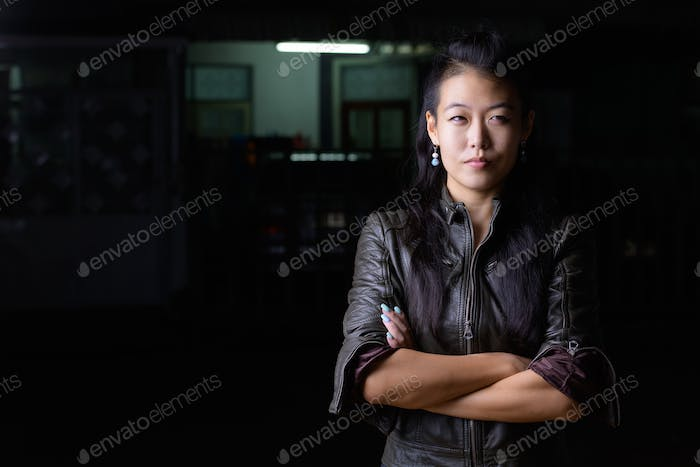 Beautiful Asian rebellious woman thinking with arms crossed outdoors at night