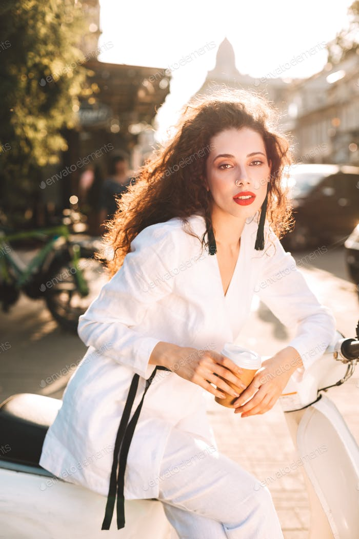Beautiful girl in white suite sitting on bike with coffee dreamily looking in camera on street